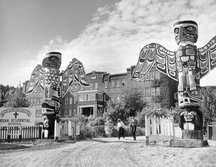 Students walk between two totem poles at St. Michael's Indian Residential School in Alert Bay, British Columbia, in a 1970 photo.