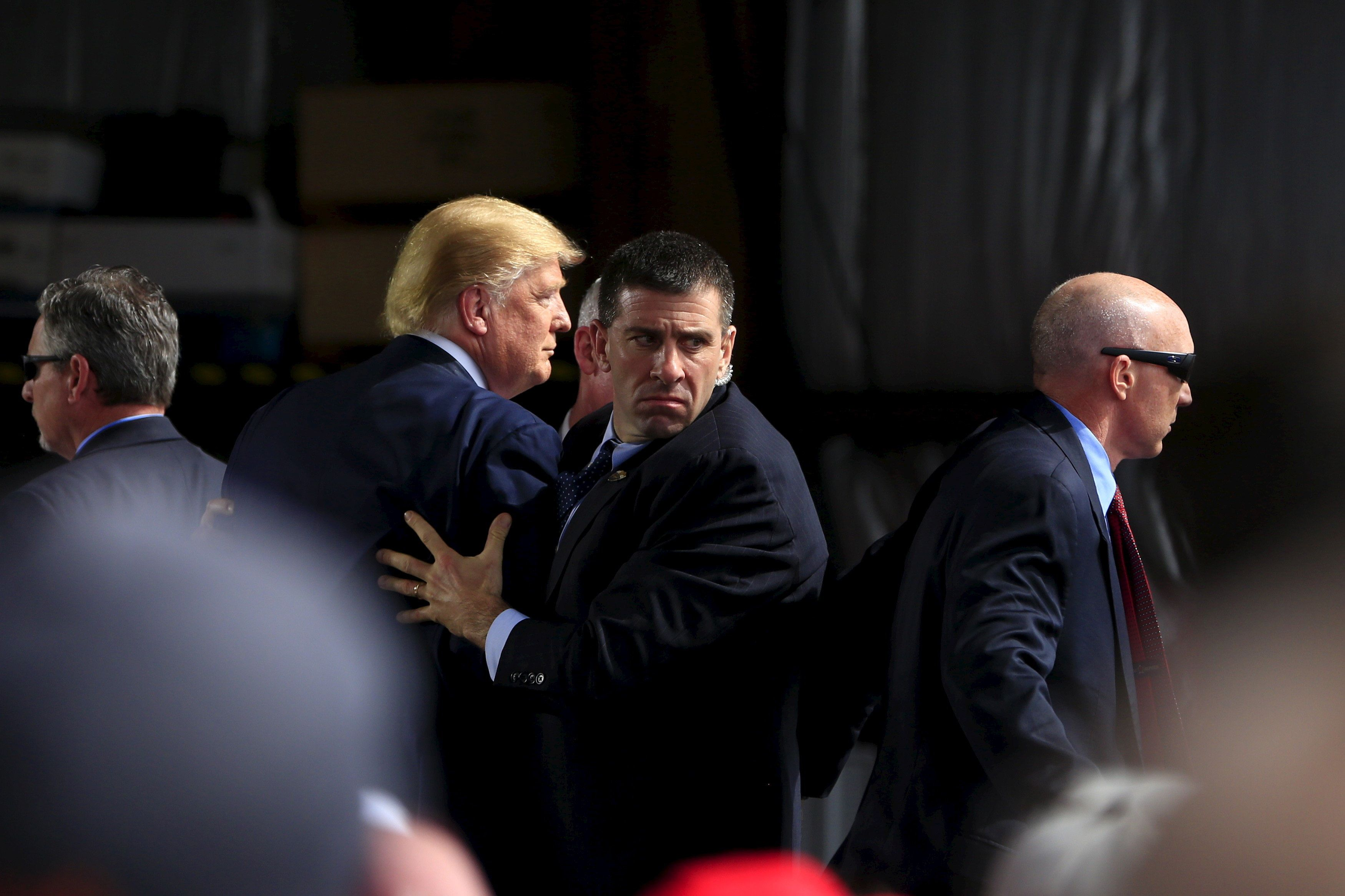Secret Service agents surround U.S. Republican presidential candidate Donald Trump during a disturbance as he speaks at Dayton International Airport in Dayton, Ohio March 12, 2016.  REUTERS/Aaron P. Bernstein      TPX IMAGES OF THE DAY