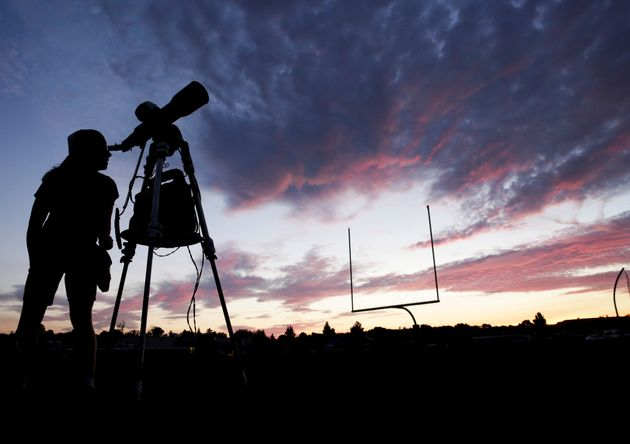 A woman looks through a telescope on the football field at Madras High School the evening before a solar...