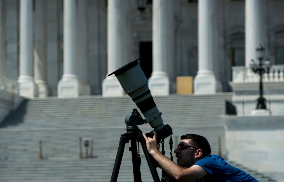 A news photographer adjusts his telephoto lens equipped with a filter in front of the U.S. Capitol on Monday, Aug. 21, 2017,