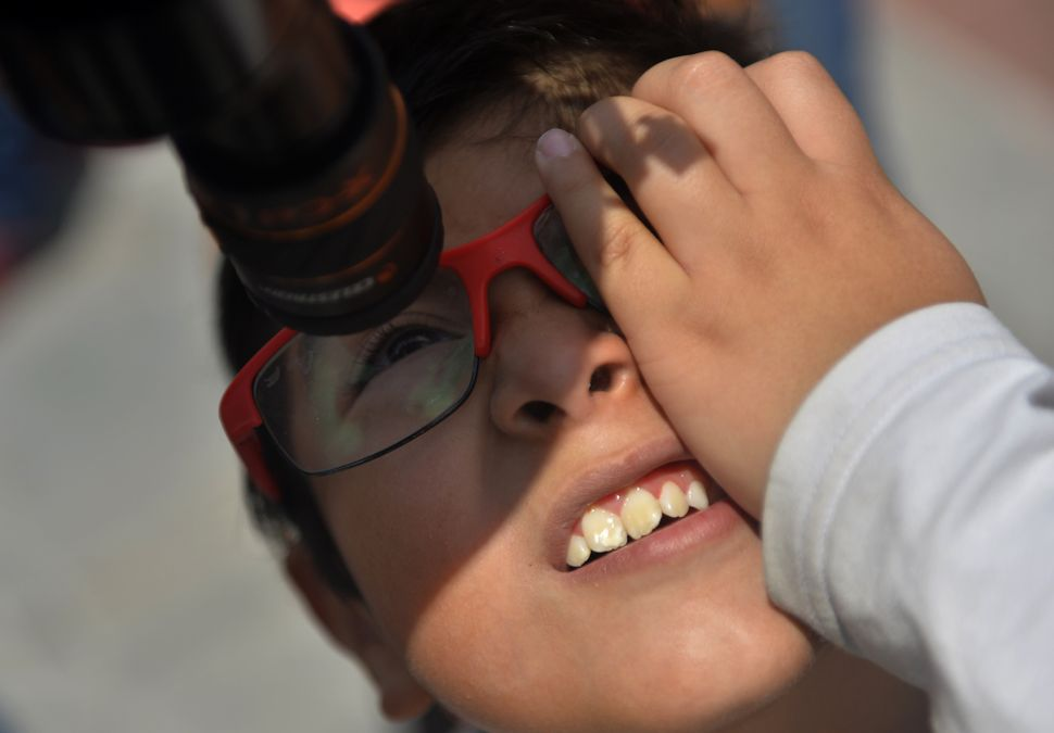A Mexican boy looks through a telescope at the beginning of the solar eclipse, at the esplanade of the Museum of Natural Hist