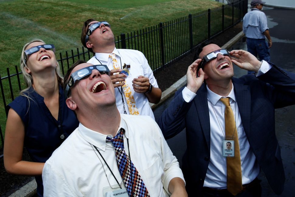 Members of the media watch the solar eclipse at the White House.