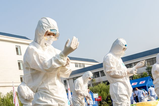 Health workers act in an exercise dealing with an outbreak of H7N9 avian flu on June 17 in Hebi,