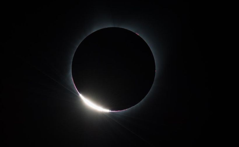 During a total solar eclipse, the moon passes in front of the sun, slowly blocking out its light and making the day look like