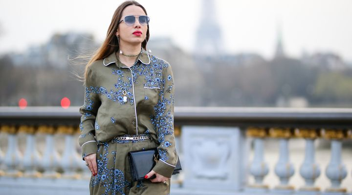 Maria Rosaria Rizzo, fashion blogger La Coquette Italienne, wears an Essentiel Antwerp green khaki pajama outfit with blue flower prints, a YSL Saint Laurent bag, Dior sunglasses, Moma Gioielli necklace and earrings, a Poiray Paris watch, and an Ursul Paris blue leather bracelet, on March 12, 2017 in Paris, France.