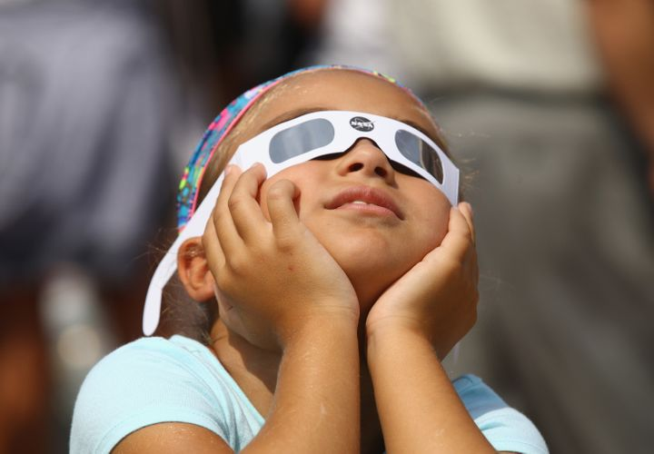 A young spectator looks skyward during a partial eclipse of the sun at the Cradle of Aviation Museum in Garden City, New York