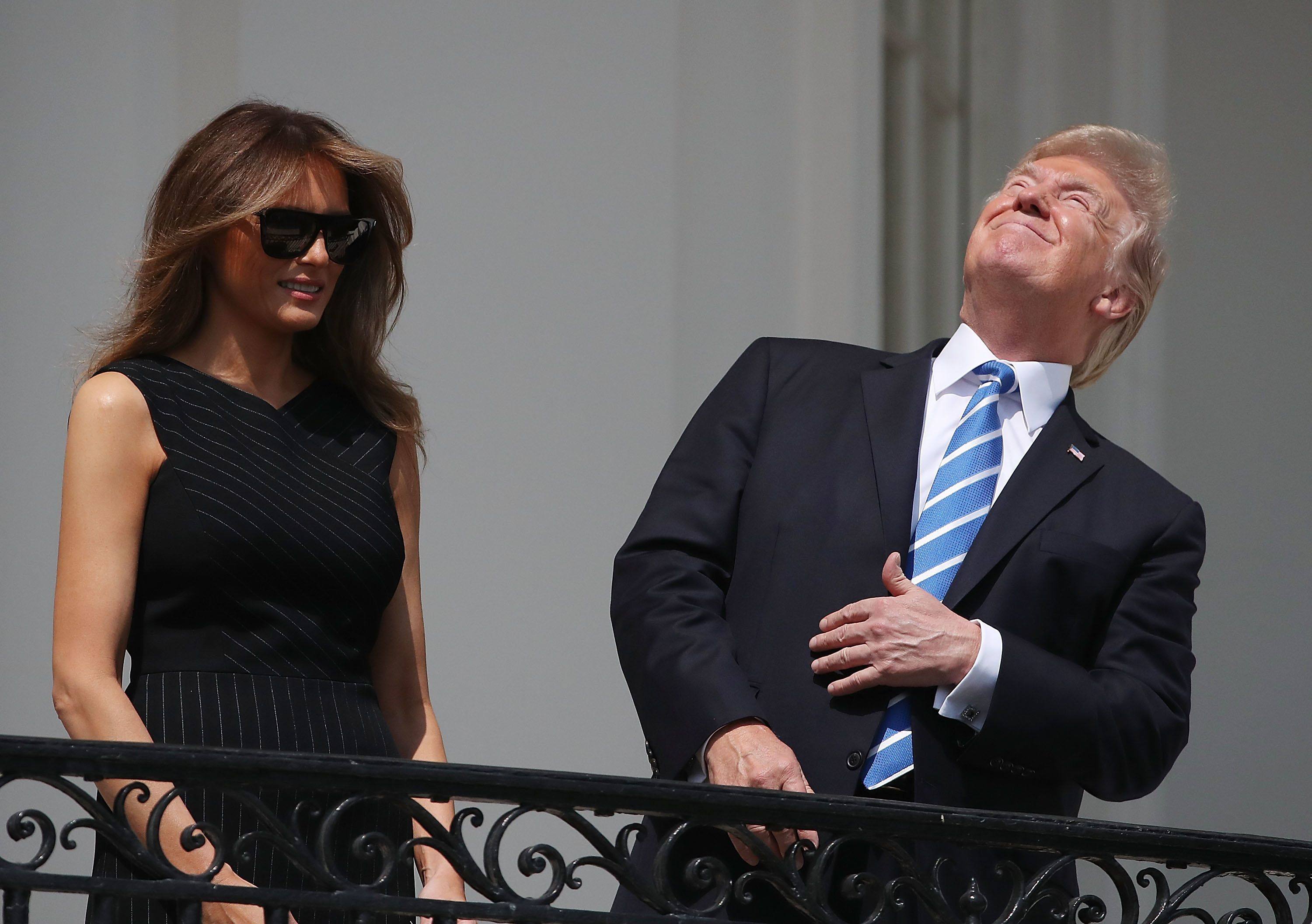 WASHINGTON, DC - AUGUST 21:  (AFP OUT) U.S. President Donald Trump looks up toward the Solar Eclipse while joined by his wife first lady Melania Trump on the Truman Balcony at the White House on August 21, 2017 in Washington, DC. Millions of people have flocked to areas of the U.S. that are in the 'path of totality' in order to experience a total solar eclipse.  (Photo by Mark Wilson/Getty Images)