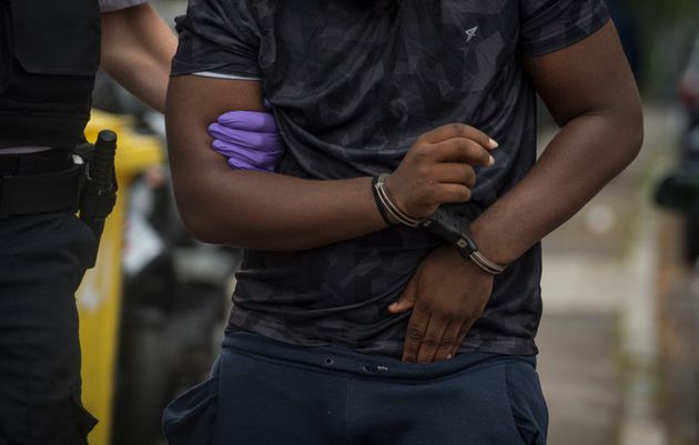 A man is led away by police after being arrested at an address in Lewisham, south east London, following...