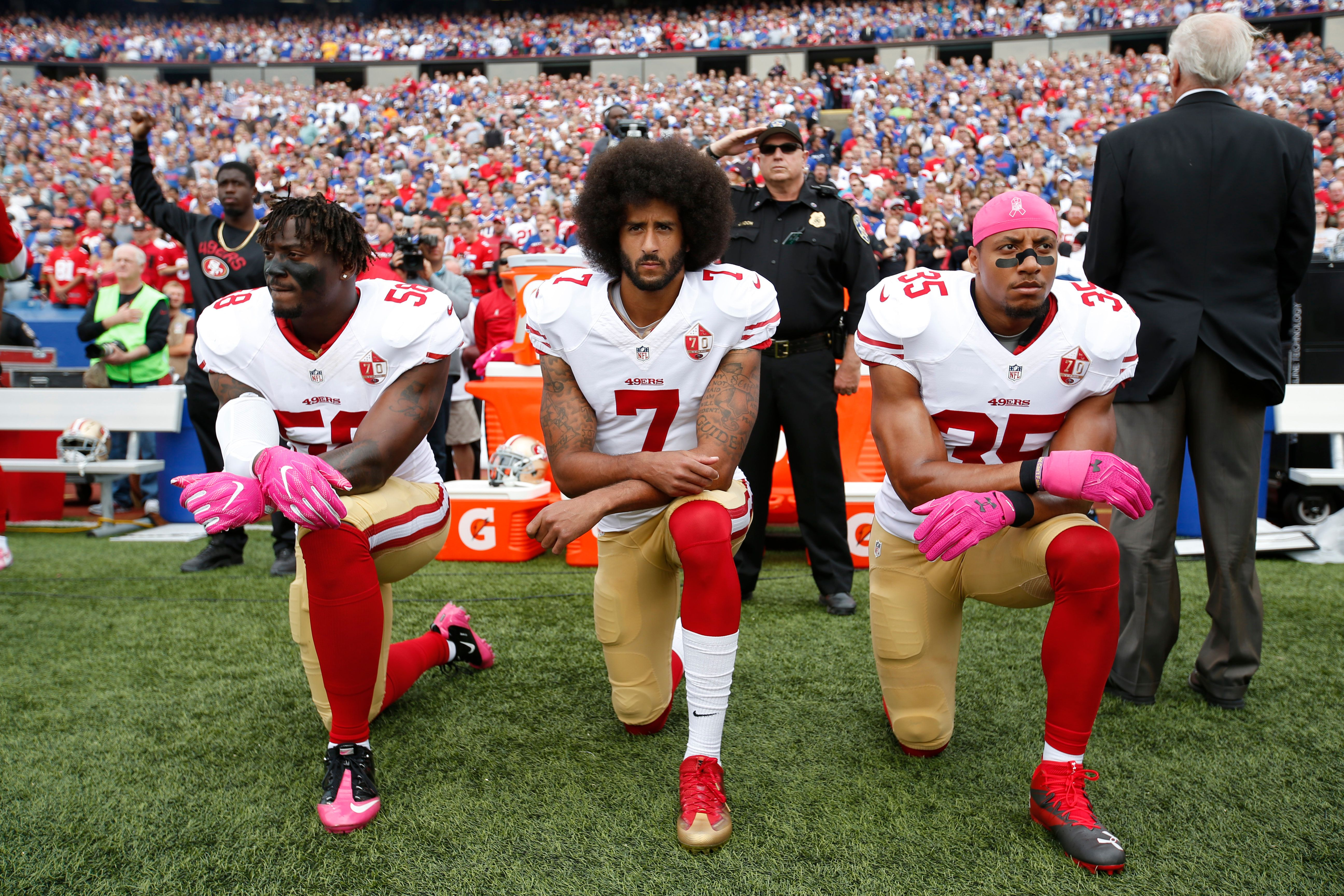 ORCHARD PARK, NY - OCTOBER 15: Eli Harold #58, Colin Kaepernick #7 and Eric Reid #35 of the San Francisco 49ers kneel in protest on the sideline, during the anthem,  prior to the game against the Buffalo Bills at New Era Field on October 16, 2016 in Orchard Park, New York. The Bills defeated the 49ers 45-16. (Photo by Michael Zagaris/San Francisco 49ers/Getty Images)