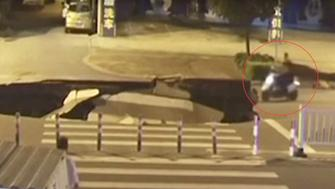 A man is seen driving a scooter straight into a sinkhole that opened up in China