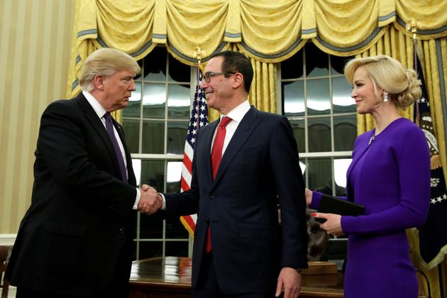 Donald Trump shakes hands with new Treasury Secretary Steve Mnuchin as Louise Linton looks on in the...