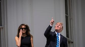 WASHINGTON, DC - AUGUST 21: President Donald Trump looks up toward the Solar Eclipse with out glasses, with first lady Melania Trump by his side, from a balcony at the White House in Washington, DC on Monday, Aug 21, 2017. (Photo by Jabin Botsford/The Washington Post via Getty Images)