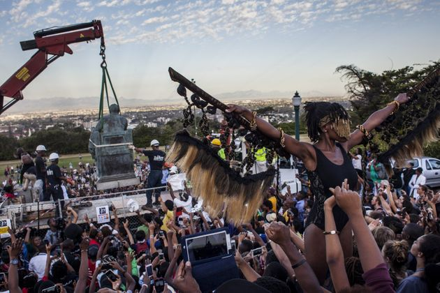 Students cheer as the Cecil Rhodes statue is removed from the University of Cape Town on April 9, 2015,...