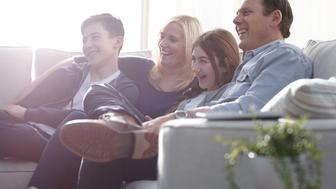 Family looking happy while watching a comedy show on television