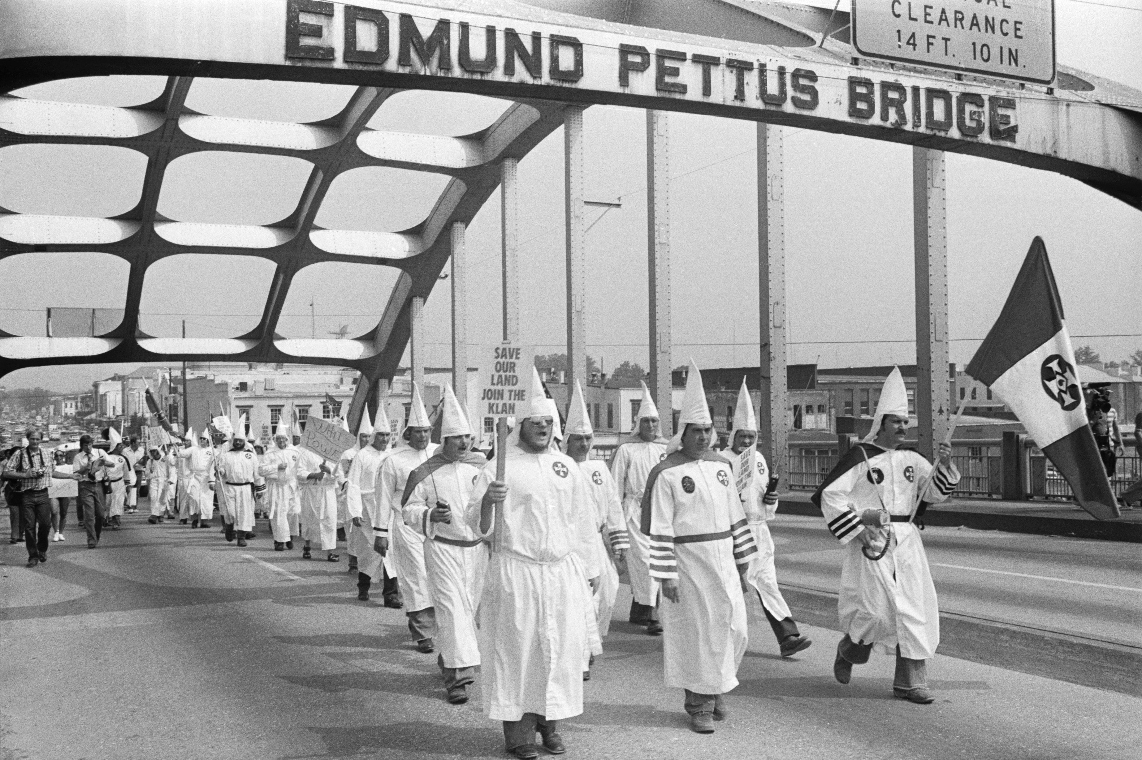 (Original Caption) 8/9/1979-Selma, AL: A small group of Ku Klux Klansmen led by Bill Wilkerson, Imperial Wizard of the Invisible Empire from Denham Springs, LA (center), march across the Edmund Pettus Bridge here 8/9 retracing Dr. Martin Luther King's march from Selma to Montgomery. The group is scheduled to end the march Sunday on the capitol steps.