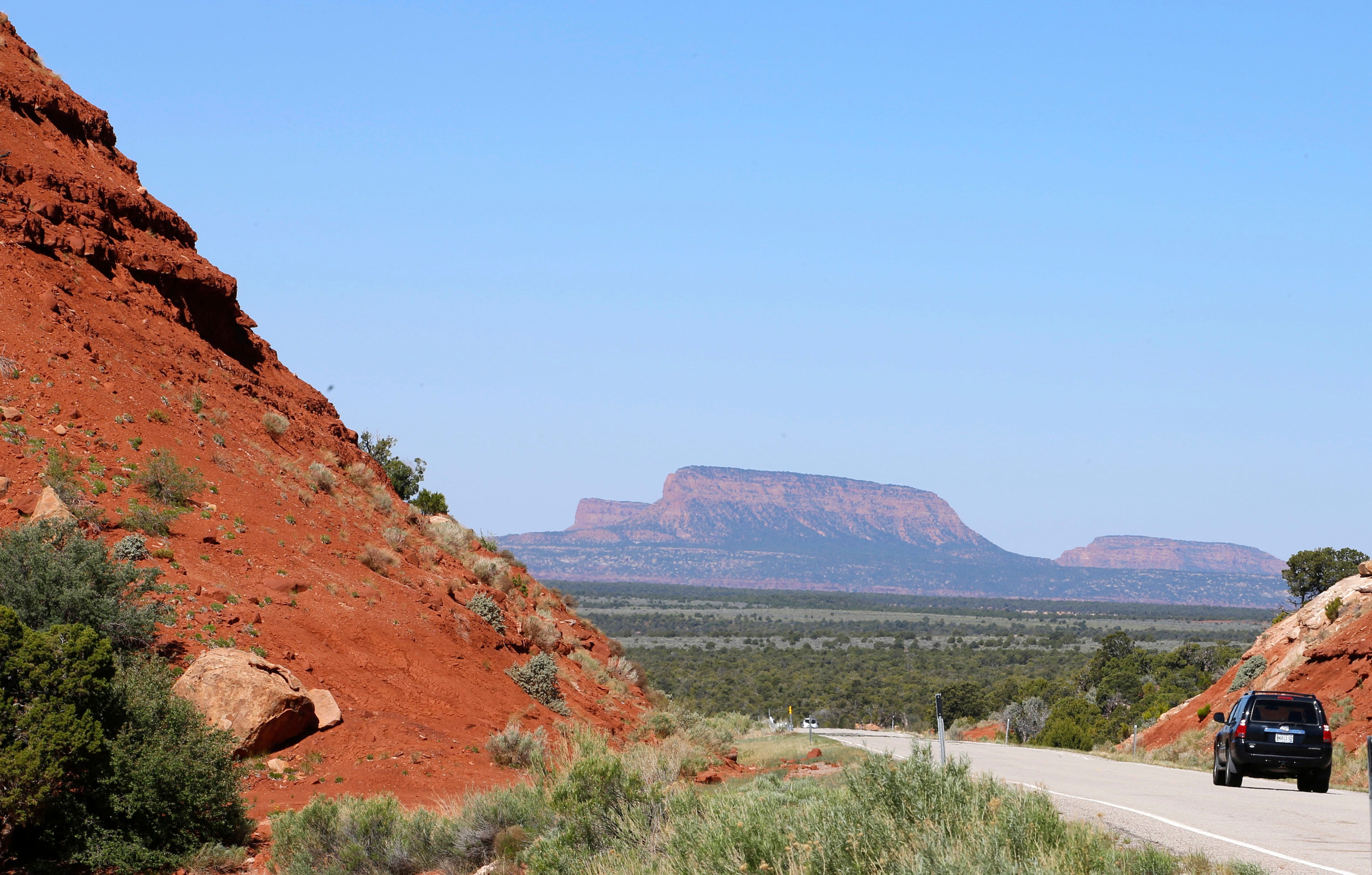 "A car drives down the Bicentennial Highway with the two bluffs known as the ""Bears Ears"" standing off in the distance in the"