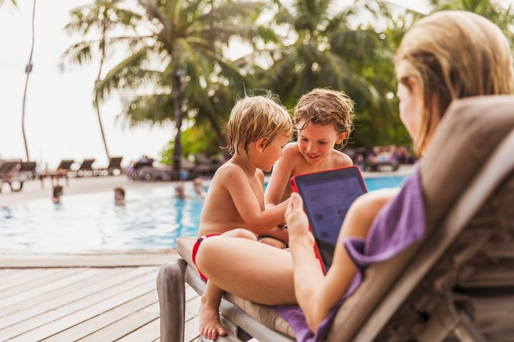 Mother and sons relaxing with digital tablet at poolside Hoxton/Paul Bradbury via Getty Images