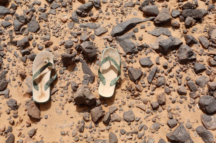 <strong>A pair of flip flops, which were left behind by a migrant, lie on the ground in the desert near the border between Algeria and Libya.</strong>