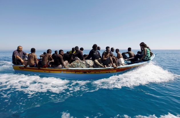 Migrants ride in a boat after they were rescued by Libyan coastguard off the coast of Gharaboli, east...