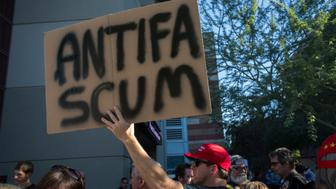 PHOENIX, AZ - AUGUST 22:  A man standing in line to enter a rally by President Donald Trump carries a sign outside the Phoenix Convention Center on August 22, 2017 in Phoenix, Arizona. An earlier statement by the president that he was considering a pardon for Joe Arpaio, the former sheriff of Maricopa County who was convicted of criminal contempt of court for defying a court order in a case involving racial profiling, has angered Latinos and immigrant rights advocates. (Photo by David McNew/Getty Images)