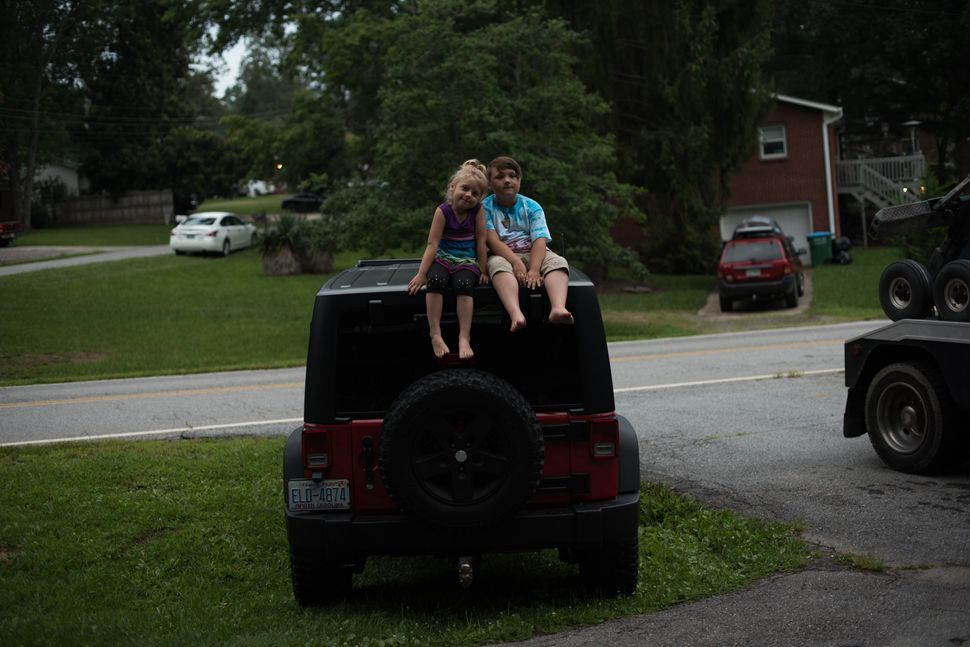 Emma and Miller on top of their dad's Jeep.