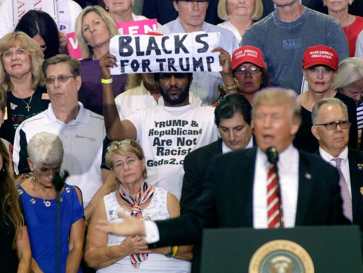 Maurice Symonette holds up his much noted sign behind President Trump at a rally in Arizona on Tuesday.