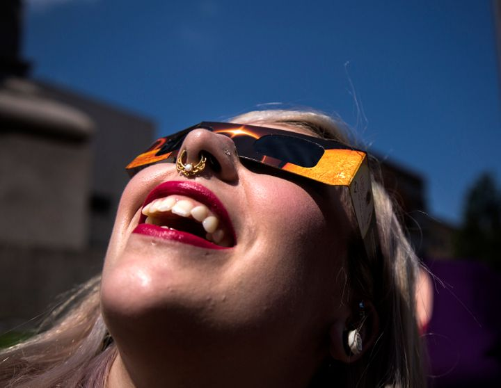 Angela Dispirito of Ware, N.H. watches the eclipse through solar glasses at Monument Square on Monday, August 21, 2017.