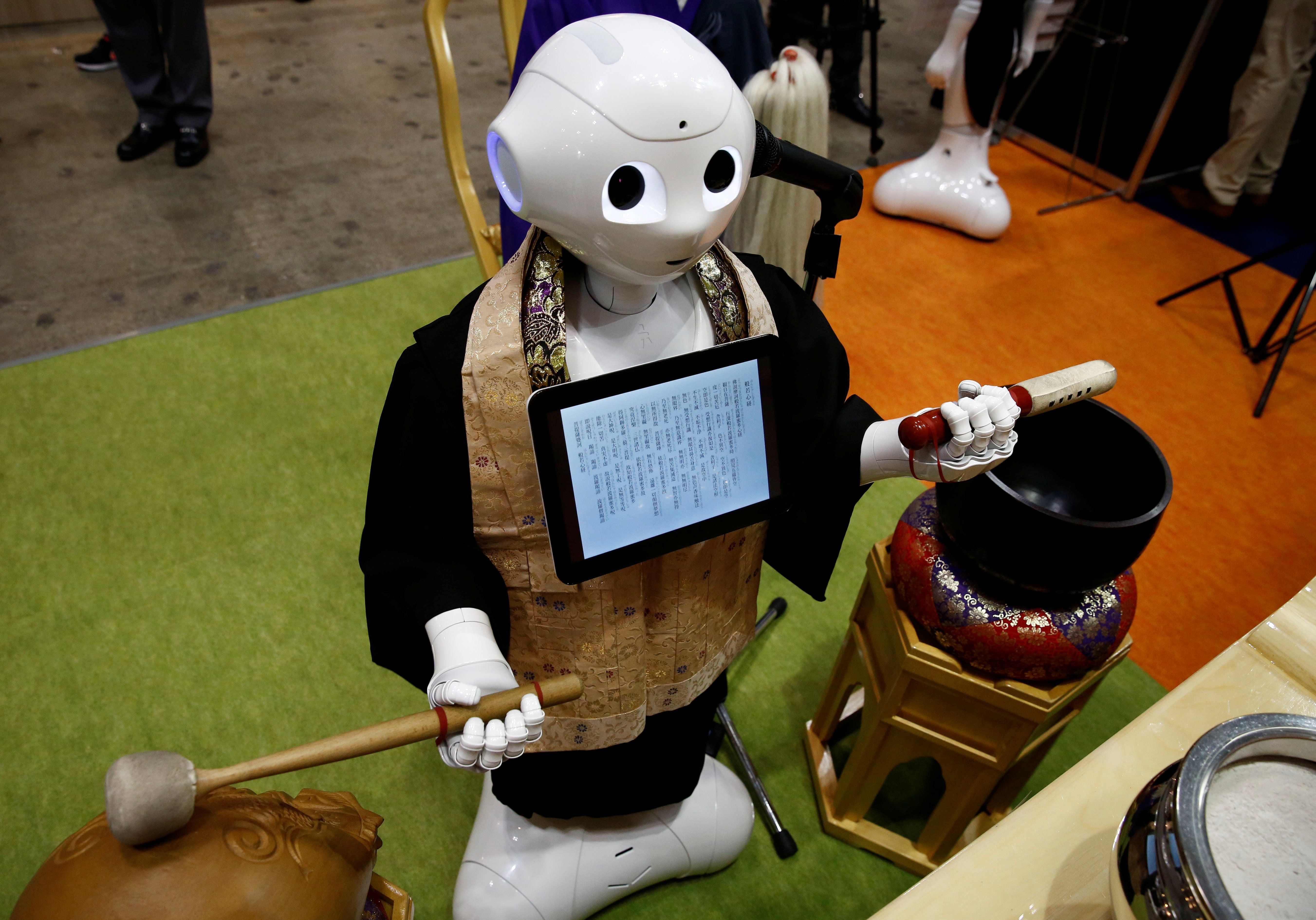 A 'robot priest' wearing a Buddhist robe chants sutras at it beats a wooden fish during its demonstration at Life Ending Industry EXPO 2017 in Tokyo, Japan August 23, 2017. REUTERS/Kim Kyung-Hoon