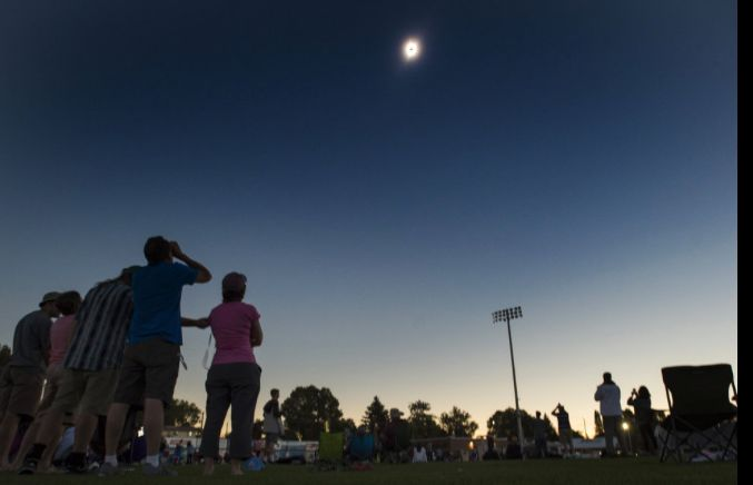 (Rick Egan | The Salt Lake Tribune; used with permission) Darkness surrounds the ball park during the totality phase of the s