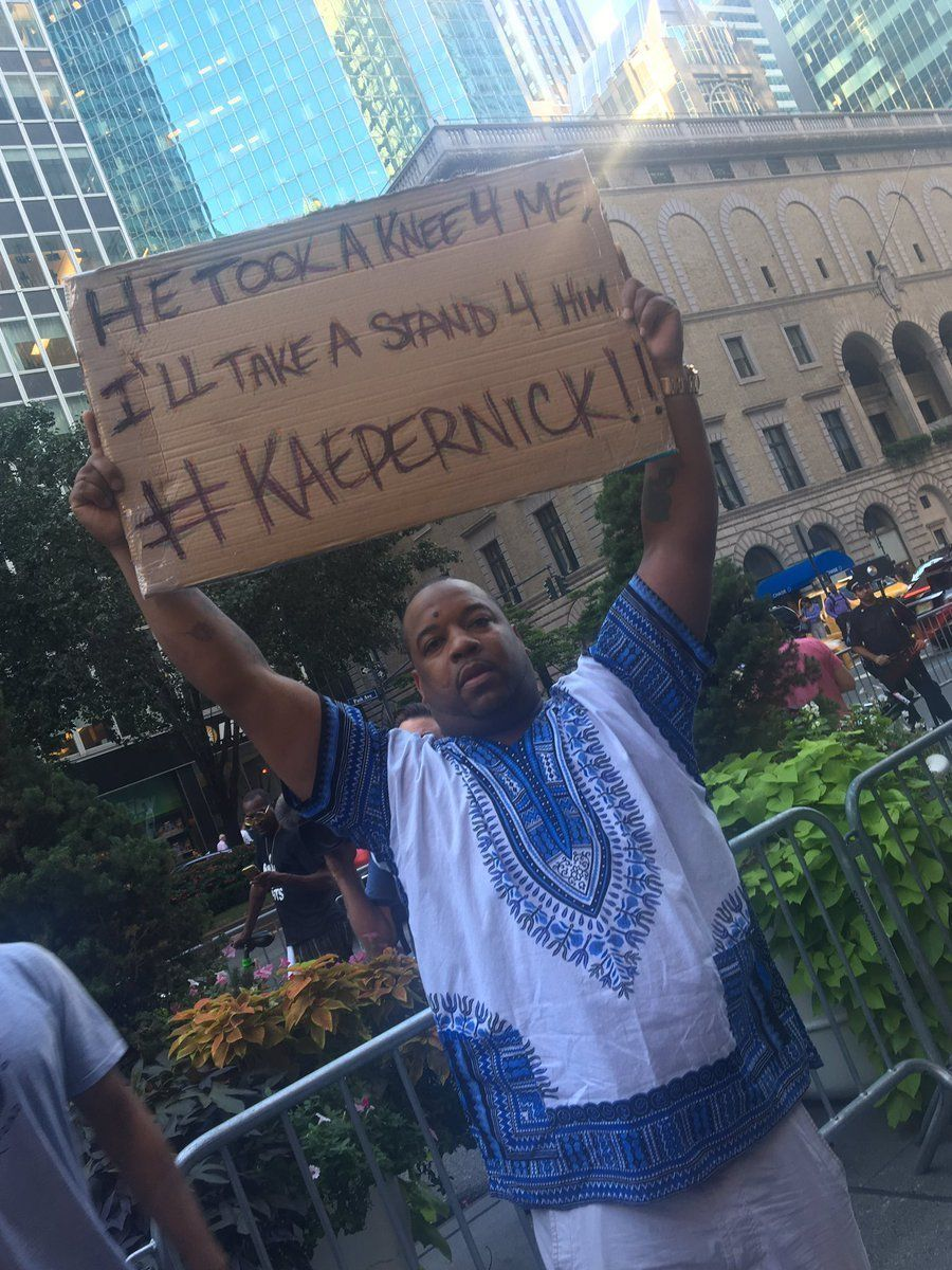 A man stands with a handmade sign supporting former 49ers quarterback Colin Kaepernick.