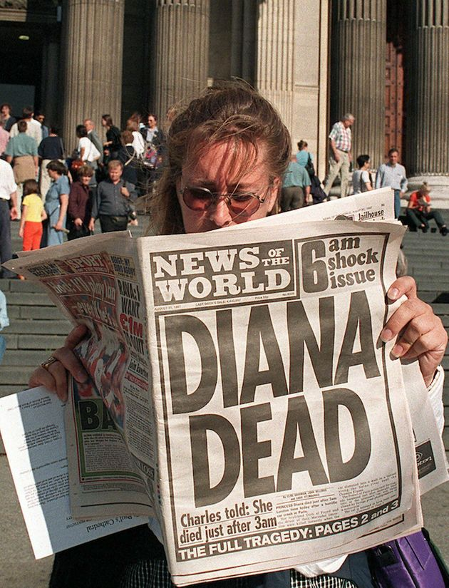 A Canadian tourist outside St Paul's Cathedral reads the News of the World's coverage on the death of