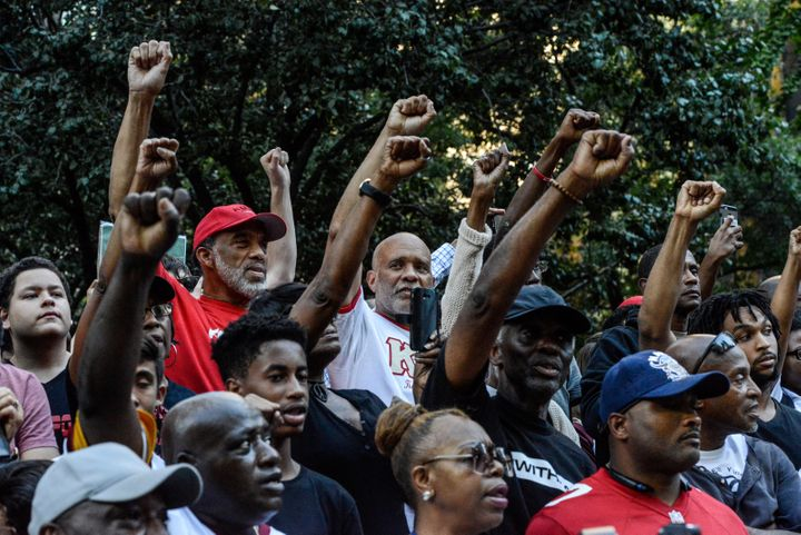 Rally attendees stand, fists raised, expressing solidarity with former San Francisco 49er Colin Kaepernick in his quest for r