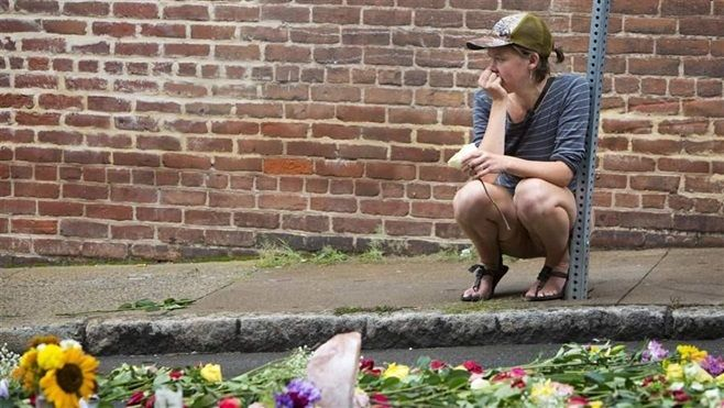 A woman leaves a flower at a memorial on the Charlottesville, Virginia, street where Heather Heyer was killed when a car ramm