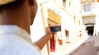 Young man walking around town taking selfie