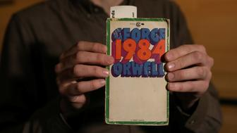 """Nicolas Rapold, editor of """"Film Comment"""" and organizer of the screening of George Orwell's """"1984"""" novel, holds the novel before the screening at the Film Society of Lincoln Center in New York, U.S., April 4, 2017. REUTERS/Shannon Stapleton"""