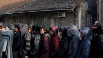 Migrants stand in line to receive free food outside a derelict customs warehouse in Belgrade, Serbia December 21, 2016. REUTERS/Marko Djurica