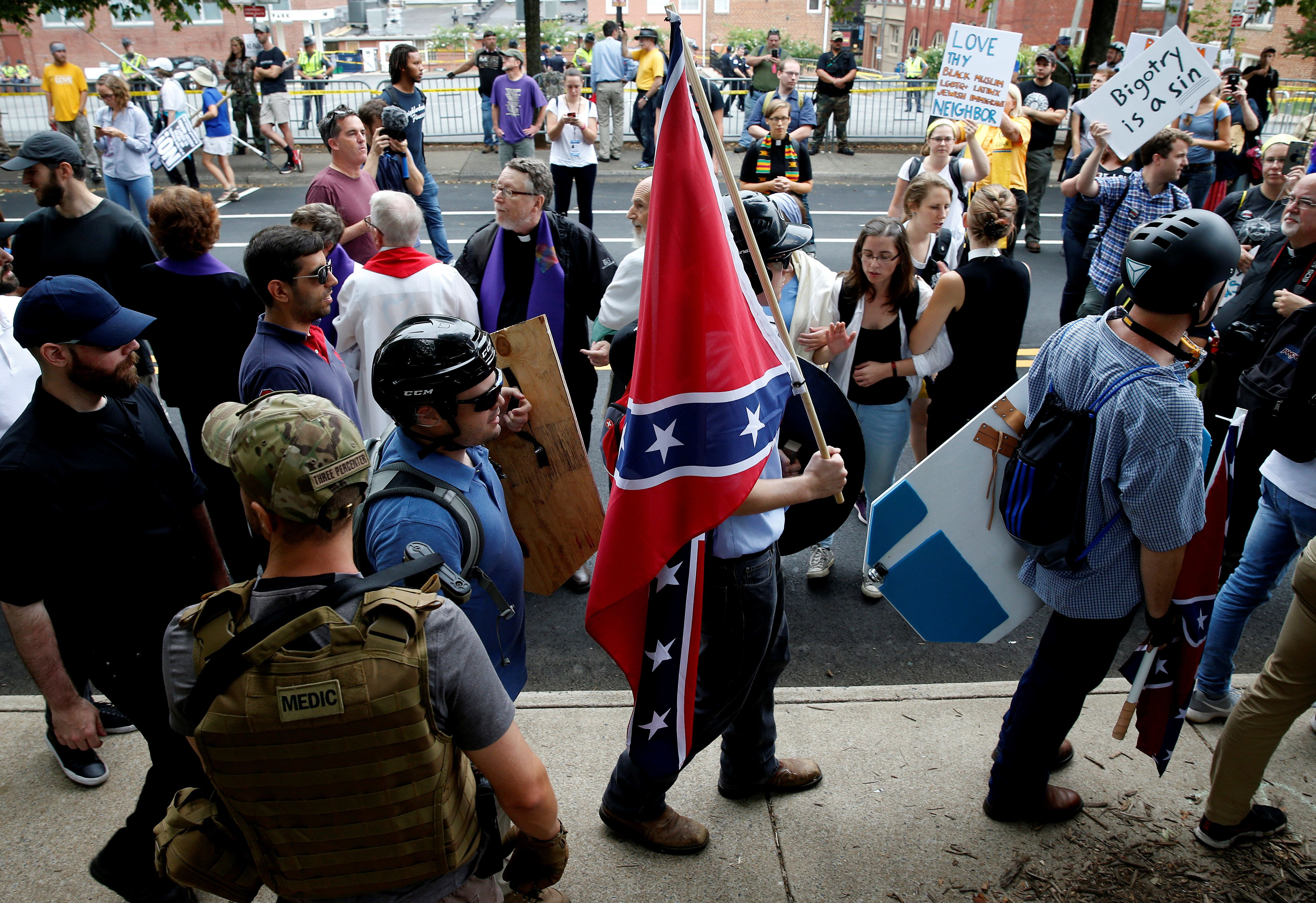 A white nationalist carries the Confederate flag as he walks past counter-demonstrators in Charlottesville, Virginia, on Aug.