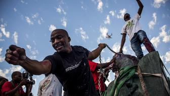CAPE TOWN, SOUTH AFRICA - APRIL 09: Students cheer after the Cecil Rhodes statue was removed from the University of Cape Town on April 9, 2015 in Cape Town, South Africa. The statue of British colonialist Cecil John Rhodes was removed from the University of Cape Town as a result of a month long protest by students citing the statue 'great symbolic power' which glorified someone 'who exploited black labour and stole land from indigenous people'. (Photo by Charlie Shoemaker/Getty Images)