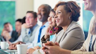 Mid adult African American businesswoman is smiling while attending a job seminar or job training business conference. She s taking notes while listening to a speaker. She is dressed in smart business casual clothing and is sitting next to diverse group of professional coworkers.
