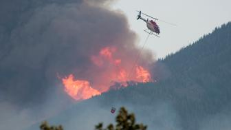 A helicopter with a water bucket passes below torching on the ridge above Pine Creek , Montana while battling the Pine Creek fire 9 miles south of Livingston, Montana in the Gallatin National Forest. The fire started on the afternoon of August 29, 2012 and quickly spread to 3,000 acres. Some houses were lost. (Photo by William Campbell/Corbis via Getty Images)