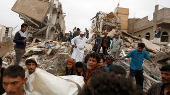 People carry the body of woman they recovered from under the rubble of a house destroyed by a Saudi-led air strike in Sanaa, Yemen August 25, 2017. REUTERS/Khaled Abdullah