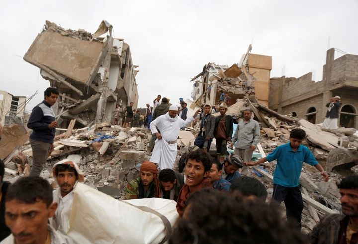 People carry the body of woman they recovered from under the rubble of a house destroyed by a Saudi-led air strike in Sanaa,