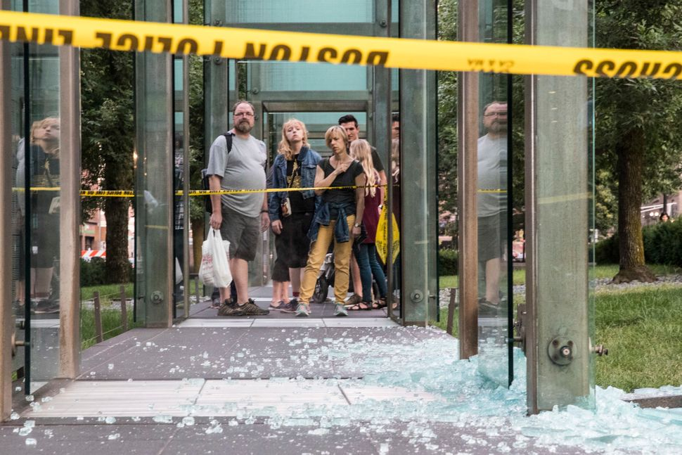 Passers-by look at glass shards on the ground from the New England Holocaust Memorial in Boston after it was vandalized on Au