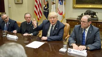 U.S. President Donald Trump, second right, speaks during a listening session with Chuck Canterbury, national president of the Fraternal Order of Police, second left, and James Pasco, senior sdvisor to the national president of the Fraternal Order of Police, right, in the Roosevelt Room of the White House in Washington, D.C., U.S., on Tuesday, March 28, 2017. Trump will sign an executive order Tuesday that will in part reverse two main planks of federal efforts under President Barack Obama to adapt to climate change, a senior White House official told reporters. Photographer: Ron Sachs/Pool via Bloomberg