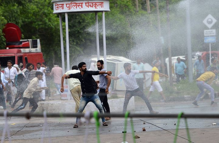 Supporters of Indian religious leader Gurmeet Ram Rahim Singh throw stones at security forces as they are sprayed with a wate