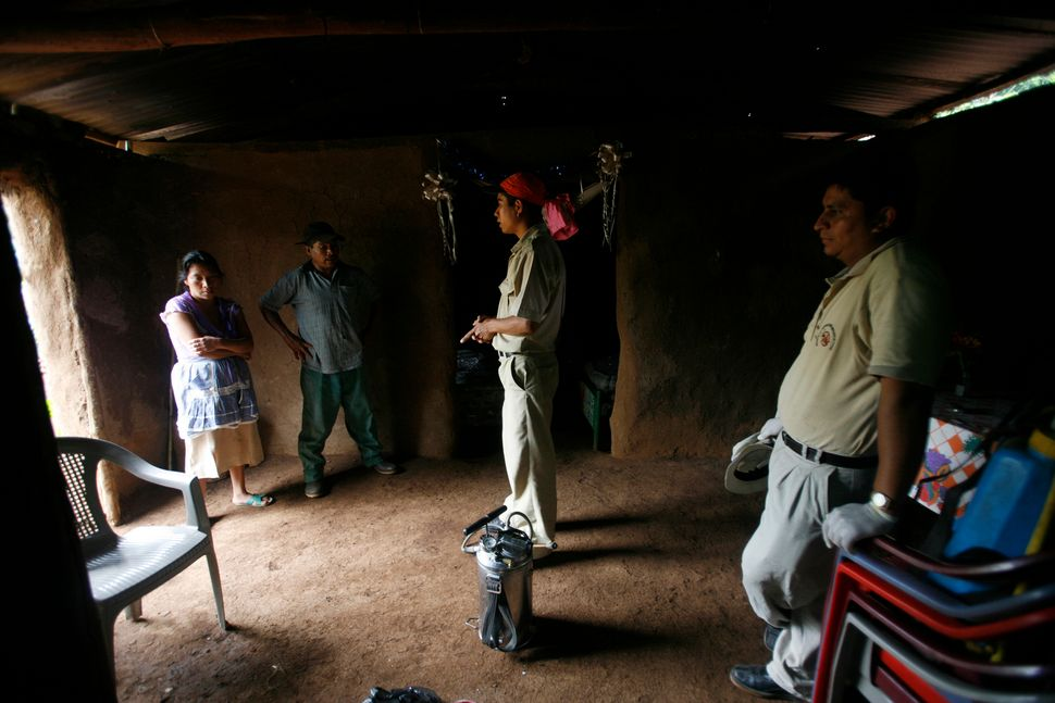 Guatemalan health inspectors speak to a family before fumigating their adobe hut, which is infested with kissing bugs.