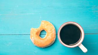 Fresh donut with coffee on old blue wooden table with copy space.
