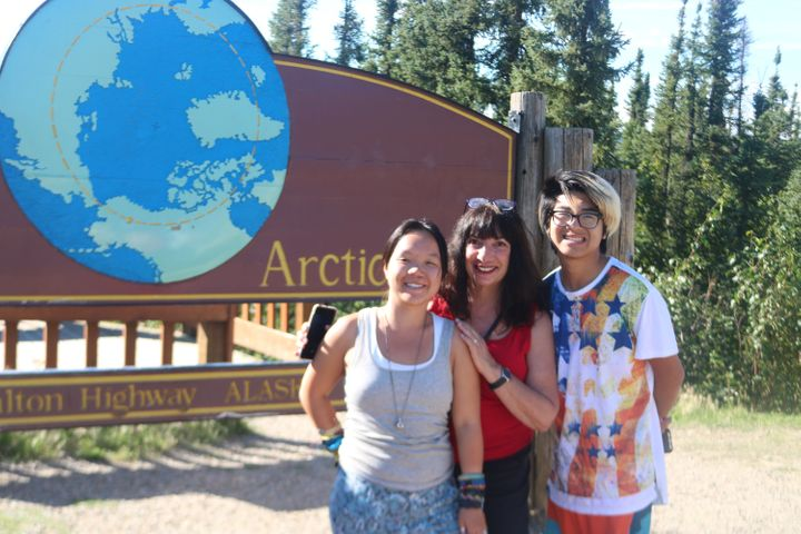 The author and her children in front of the marker for the Arctic Circle.