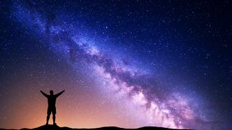 Purple Milky Way with silhouette of a standing man with raised up arms on the hill. Night landscape with beautiful galaxy. Universe. Night starry sky with Milky Way and yellow light