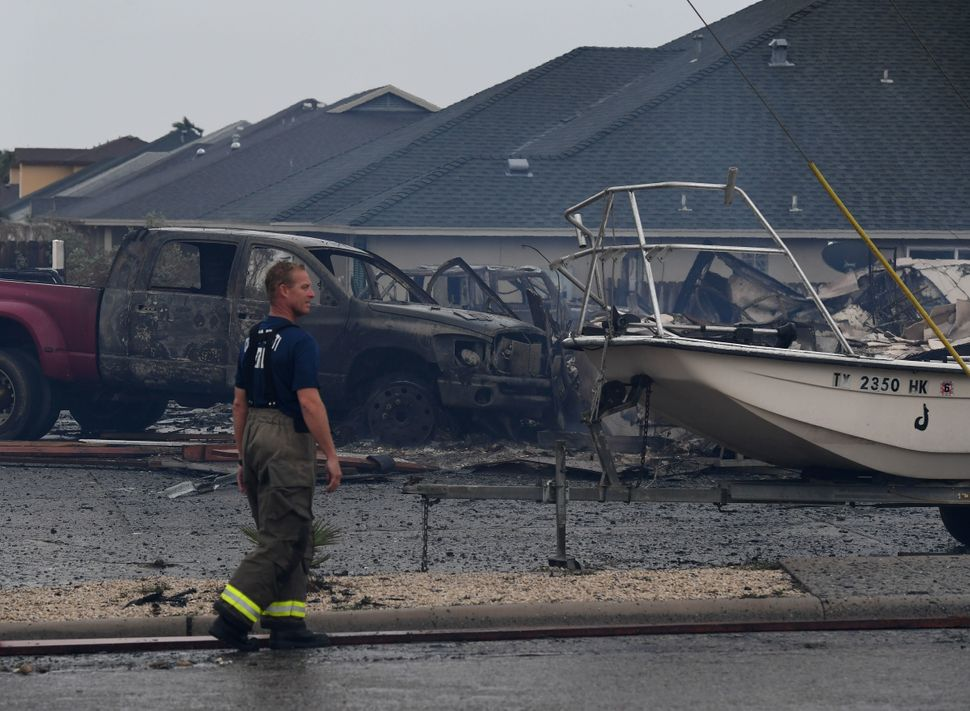 A fireman walks by a burnt-out car that caught fire in Corpus Christi.